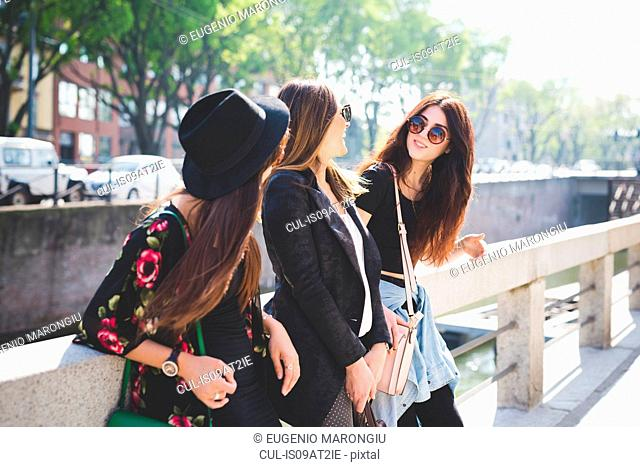 Three young female friends chatting on city riverside