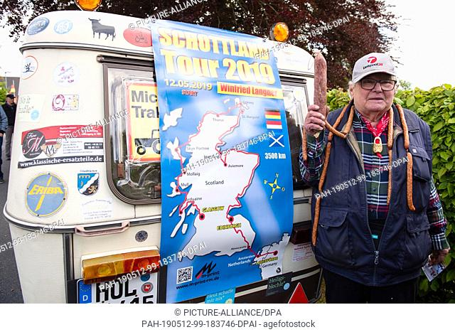 """12 May 2019, Lower Saxony, Lauenförde: The pensioner Winfried Langner, known as """"""""Deutz-Willi"""""""", stands before the departure with a Mettwurst in his hand on his..."""