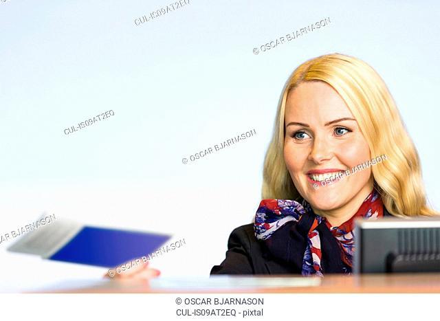 Female check in desk staff handing over boarding pass