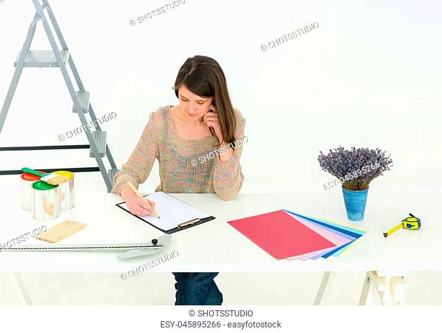 Creative people workplace. Close-up view of brunette young designer woman working with colour palette at office desk. Interior shot