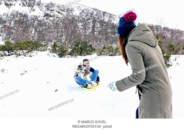 Man and woman having funwith sled and dog in the snow