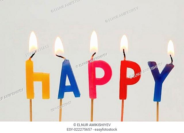 Burning candles with the word Happy