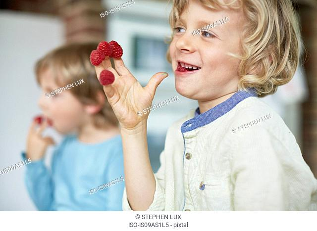 Two boys eating raspberries off fingertips