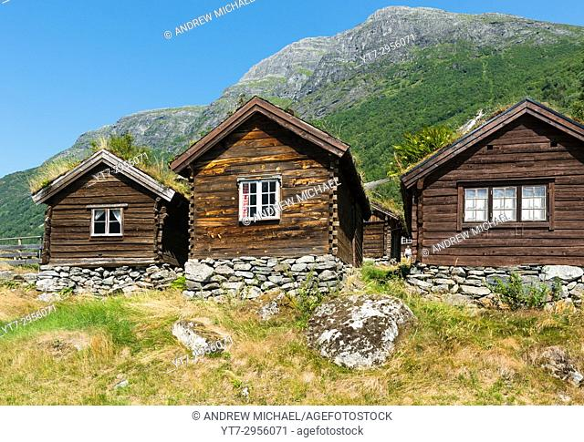 A view across Lovatnet Lake, a traditional Norwegian house sits in the foreground topped with sod roof