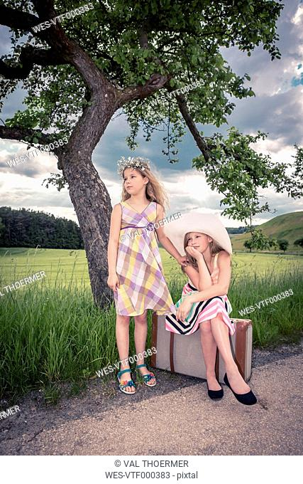 Germany, Bavaria, Girls with old suitcase waiting at roadside