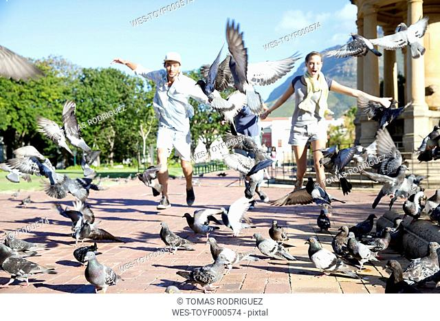 Enthusiastic young couple chasing pigeons