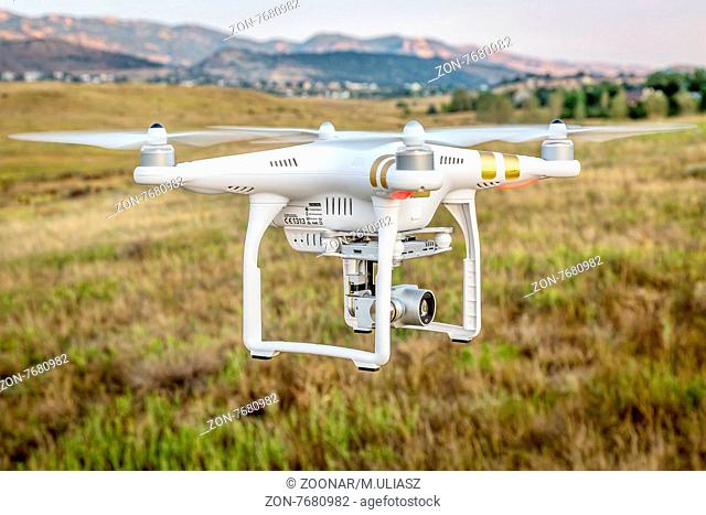 FORT COLLINS, CO, USA, SEPTEMBER 1, 2015: Radio controlled Phantom 3 quadcopter drone is flying with a camera over foothills of Rocky Mountains