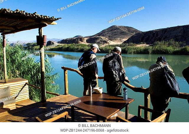 Namibia Africa three tourists looking at Kunene River from resort of Serra Cafema Camp resort looking at Angola across river in safari vacation