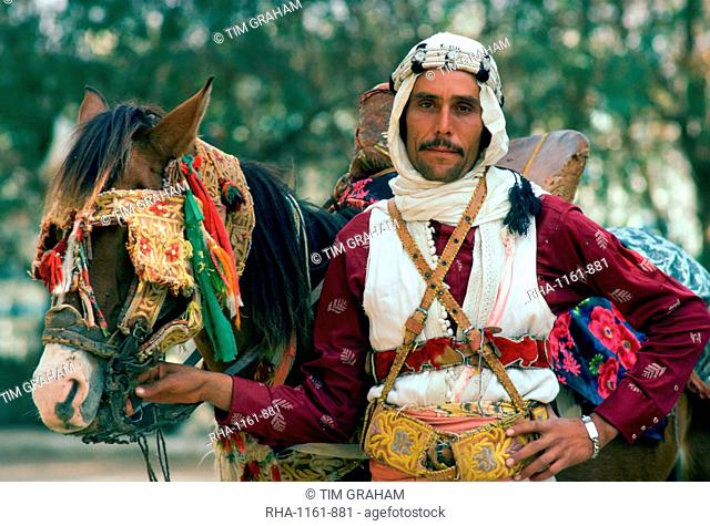 A horseman in traditional dress holding his horse which has eye defenders against the sun and dust
