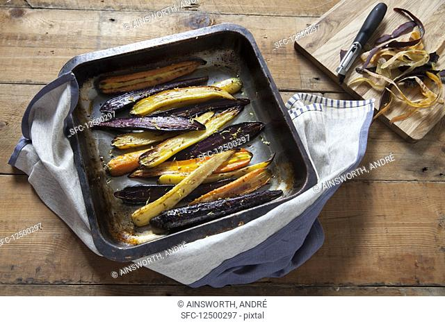 Roasted heritage carrots with lemon and cumin in a baking tray