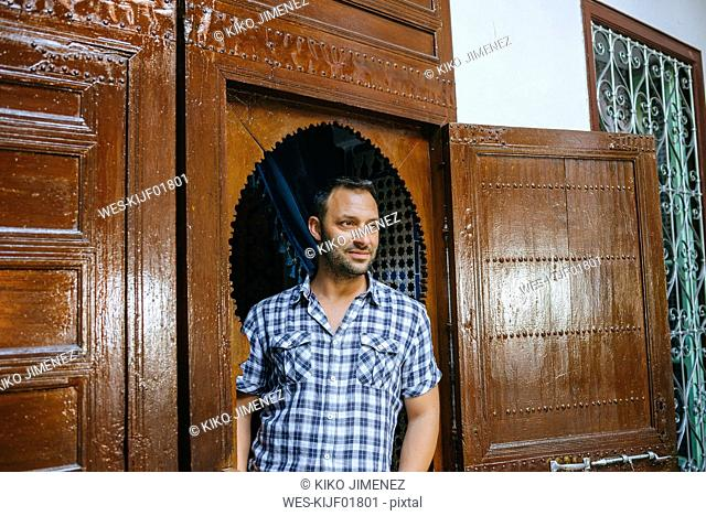 Morocco, portrait of tourist standing in typical arabic door frame