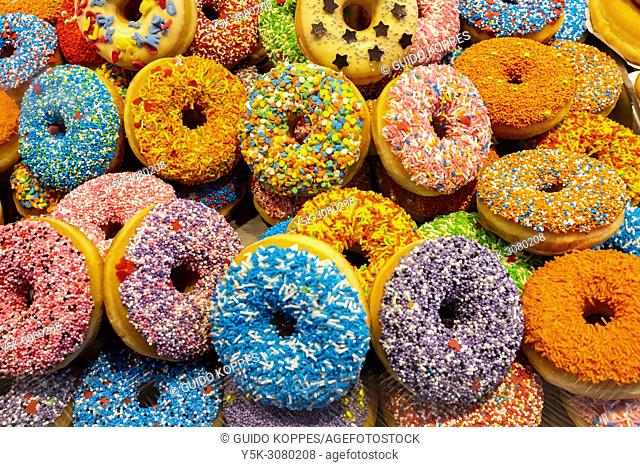 Rotterdam, Netherlands. Stack of very colorful donuts for sale on a Market Hall market stand down town. Creativity when making donuts is booming