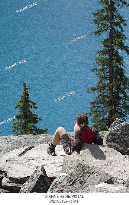 Woman looking down on Moraine Lake in Banff National Park, Alberta, Canada