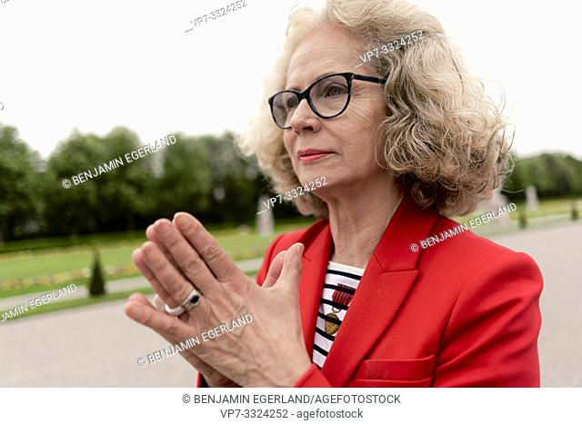 senior woman (67 years old) with folded hands in park, in Nymphenburg, Munich, Germany