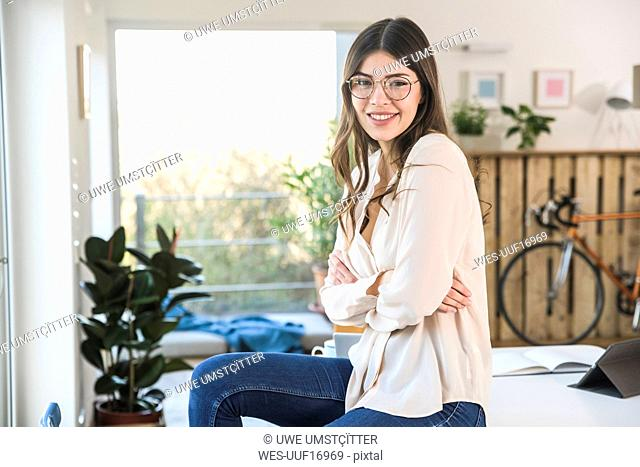 Portrait of smiling young woman sitting on table at home