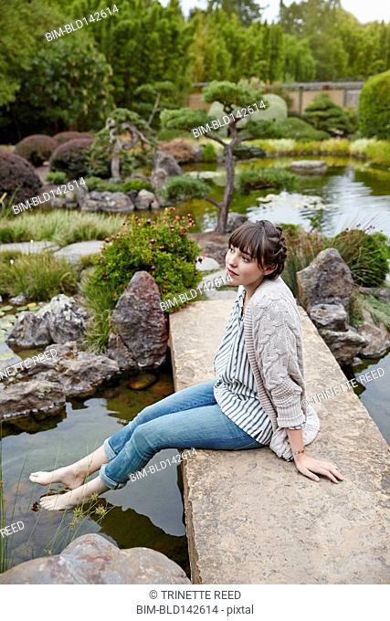 Caucasian woman dipping feet in garden pool
