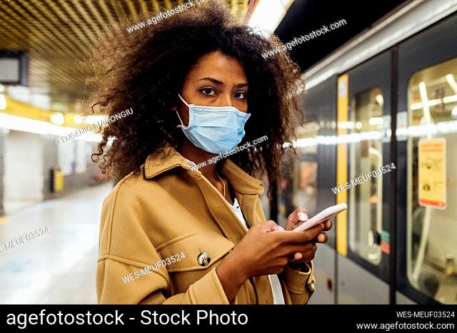 Young woman with protective face mask holding mobile phone while standing in subway