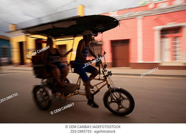 Dynamic scene of a bici taxi driver in front of colonial houses in the city center, Trinidad, Sancti Spiritu Province, Cuba, West Indies, Central America