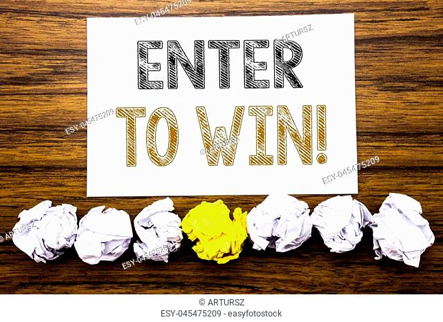 Word, writing Enter to Win. Concept for Winning in Competition Written on sticky paper reminder, wooden background with sticky