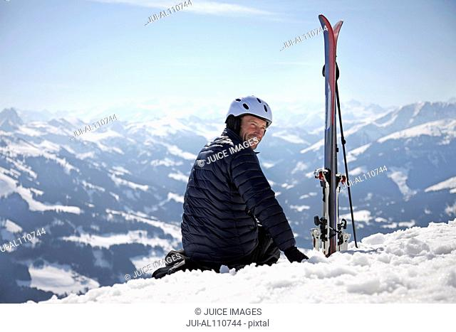 Mature man sitting in snow next to skis on mountain