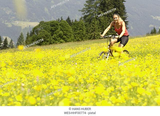 Young woman mountain biking in field