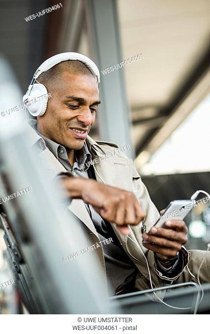 Man wearing headphones holding smartphone