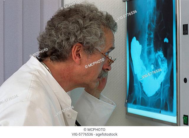 Arzt betrachtet eine Roentgenbild vom Becken und von der Wirbelsaeule, Hamburg 2002 - Hamburg, Germany, 20/04/2002