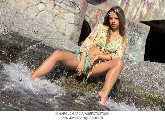 Sexy woman with a beautiful body wetting the feet on the river water's and posing sensually in Yalta, Crimea