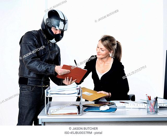 Businesswoman signing for courier