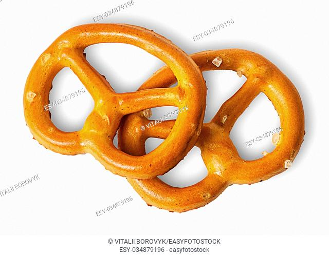 Two crunchy pretzels with salt on each other isolated on white background