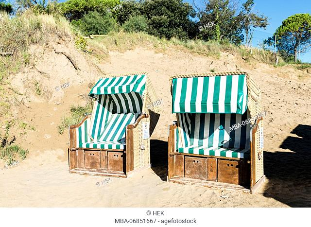 two green and white striped beach chairs on the beach of Lignano