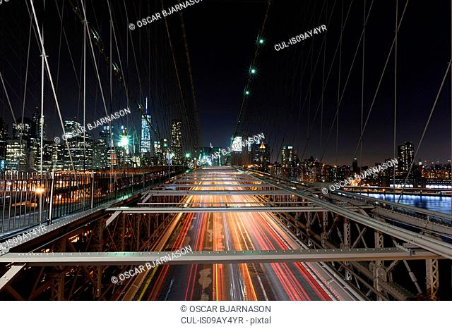 Elevated view of traffic light trails crossing Manhattan Bridge at night, New York, USA