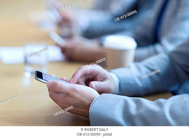 Close up of businessman using cell phone in meeting