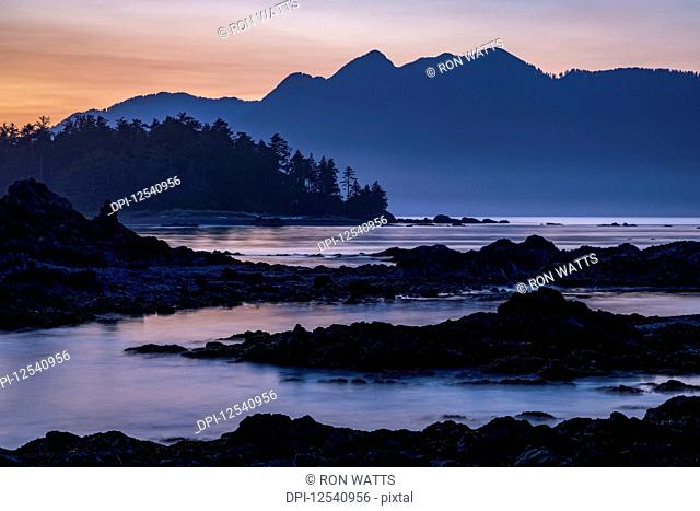Dusk falls over Vancouver Island viewed from an islet in Nuchatlitz Provincial Park; British Columbia, Canada