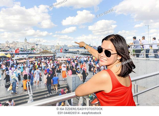 Beautiful Chinese woman shows Galata Tower at Eminonu district in Istanbul, Turkey