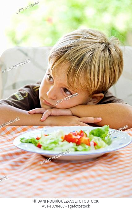 Portrait of a boring boy with a plate of salad