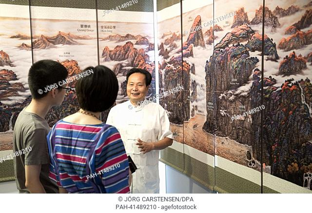 Chinese painter Liu Zuozhong (R) explains his work about the Three Gorges to visitors at the Chinese Cultural Center in Berlin, Germany, 02 August 2013