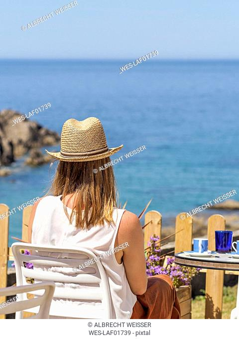Woman sitting at the sea, drinking coffee