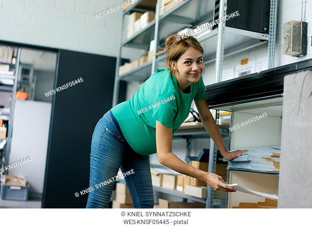 Portrait of smiling pregnant woman working in office