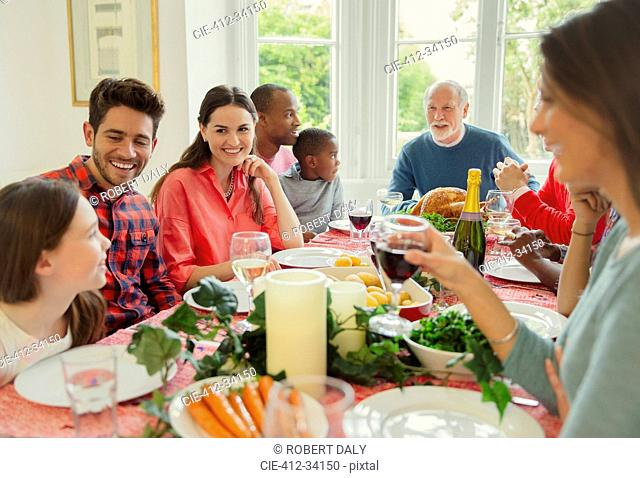 Multi-ethnic multi-generation family enjoying Christmas dinner at table