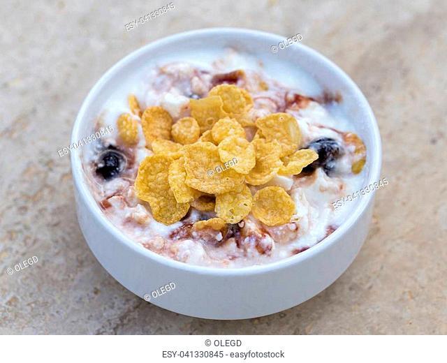 White bowl with muesli, berry, flakes, yogurt and honey, close up, healthy breakfast
