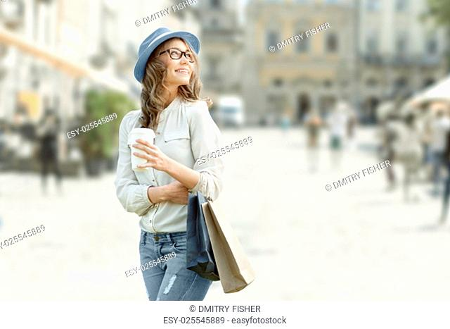 Happy young fashionable woman with shopping bags enjoying drinking coffee after shopping and holding take away coffee against urban background