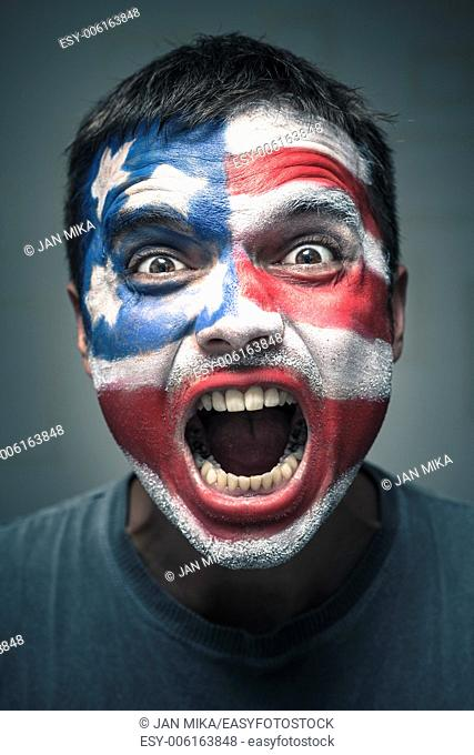 Portrait of angry man with USA flag painted on face
