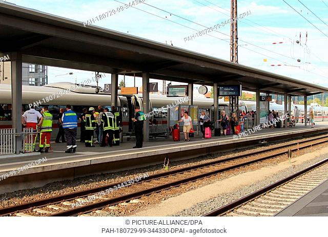 29 July 2018, Germany, Aschaffenburg: Firefighters and travellers are standing on a platform at the main station. A major police and fire brigade operation...