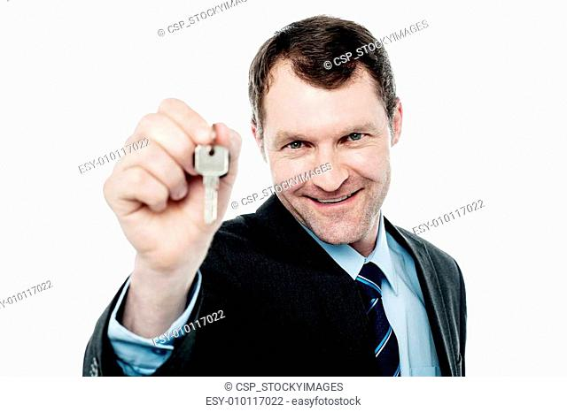 Happy businessman holding a house key