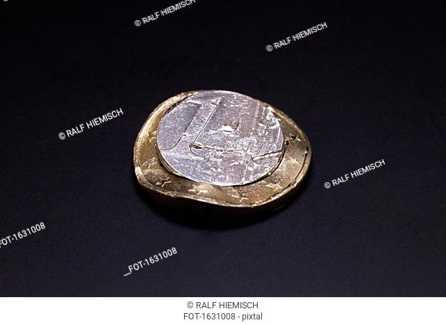 Close-up of dented one Euro coin against black background