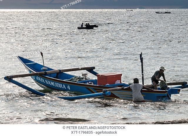 Launching fishing boats from the beach at Jimbaran, southern Bali, Indonesia