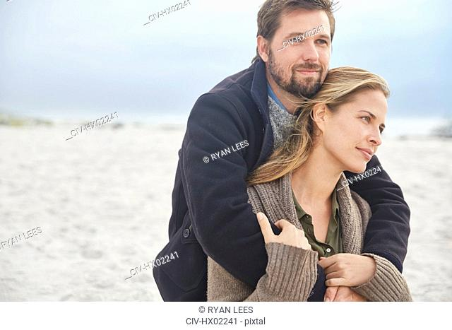 Serene affectionate couple hugging on winter beach