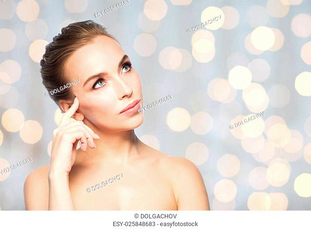 beauty, people and health concept - beautiful young woman looking up over holidays lights background