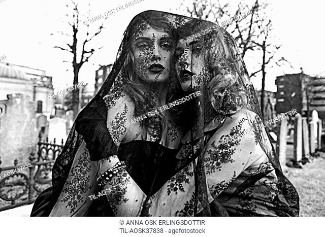 Female couple outdoors under black lace veil